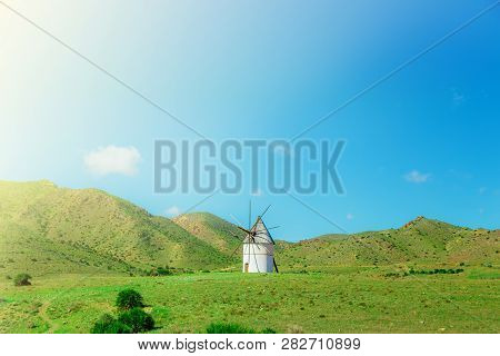 Old Windmill On The Green Lawn And Hills, Cabo De Gato, Spain