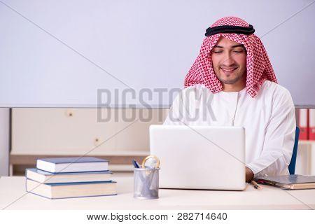 Arab teacher in front of whiteboard