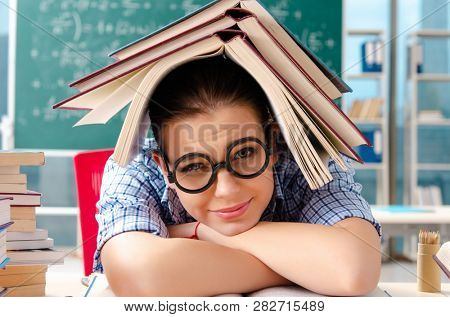 Female student with many books sitting in the classroom