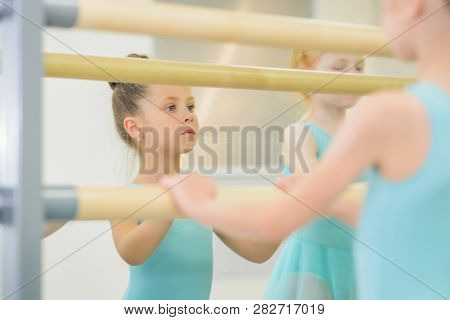 Portrait Of Little Ballerina Practicing Ballet In Studio Near Barre. Studying In Dance School.