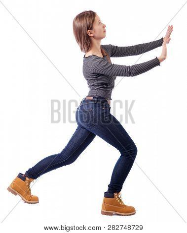 back view of woman pushes wall.  Isolated over white background. Rear view people collection. backside view of person. A girl in jeans and boots is pushing something in front of her.