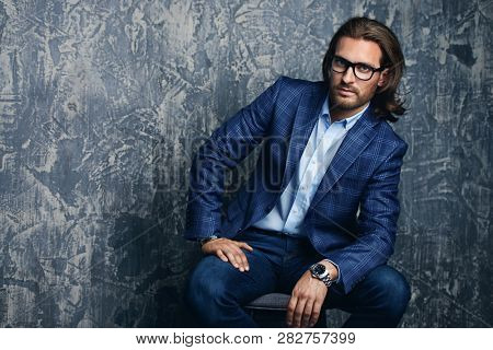 Portrait of a handsome young man in elegant classic suit and glasses. Men's beauty, fashion. Business style.