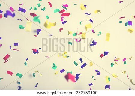 Falling confetti on creamy background. Party, birthday celebration. Colorful festive background.