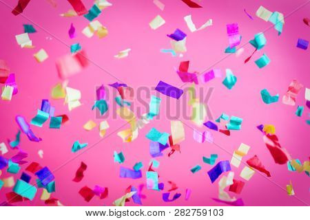 Falling confetti on pink background. Party, birthday celebration. Colorful festive background.