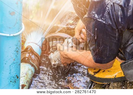 Plumber Working Repair The Broken Pipe And Replace   In Hole With Water Motion At Roadside