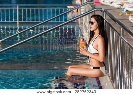 Beauty Young Slim Woman With Long Dark Hair Wearing A White Swim Suit Is Leaning On The Metal Fence