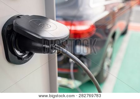 Close Up Of The Power Supply Plugged Into An Electric Car Being Charged. Electric Car Charging Stati