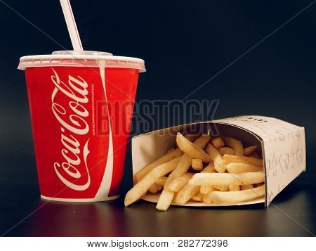 Gomel, Belarus - February 5, 2019: Coca Cola Drink And French Fries And Burger On A Dark Background.