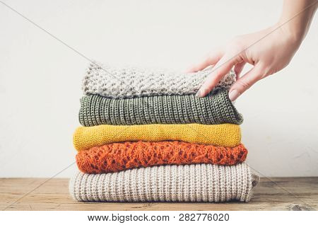 Pile Of Knitted Woolen Sweaters. Clothes With Different Knitting Patterns Folded In Stack. Warm Cozy
