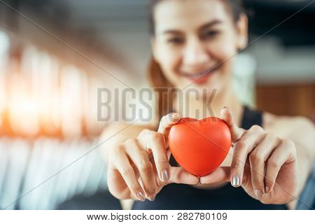 Asian Sport Woman Holding Red Heart In Fitness Or Gym Center. Medical Cadio Heart Strength Training