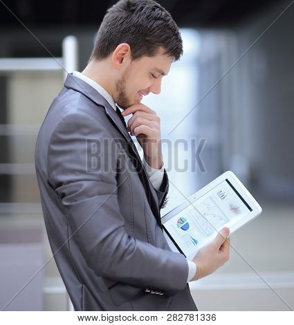 Businessman Looks At Digital Tablet Screen With The Digital Sch