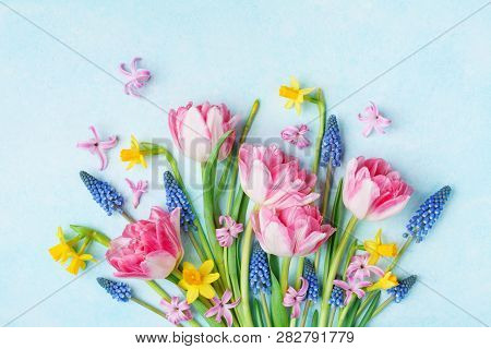Bouquet Of Beautiful Spring Flowers On Pastel Blue Table Top View. Greeting Card For International W