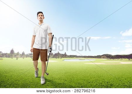 Handsome Asian Man In White Clothes Holding Iron Golf Club Walking On The Golf Course With Sand Bunk
