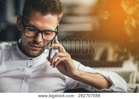 Young Businessman Sitting Relaxed On Sofa At Cafe Making A Phone Call, Waiting For Someone. Sunlight