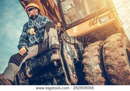 Caucasian Excavator Operator Sitting On His Excavator. Heavy Duty Ground Working Machinery. Construc