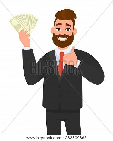 Happy Young Businessman Showing Or Holding Cash, Money, Currency Notes, Dollars Or Banknotes In Hand