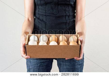 Caucasian Woman With Black Shirt Holding A Cardboard Egg Box Full Of Hen Eggs On A White Background.