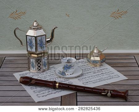 English Teacup And Saucer, Silver-plated Teapot On A Silver Stove, Sugar Bowl And Sugar Spoon With F