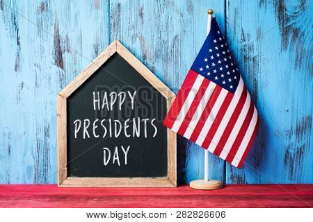 an american flag and a house-shaped chalkboard with the text presidents day written in it on a red wooden surface, against a blue wooden background