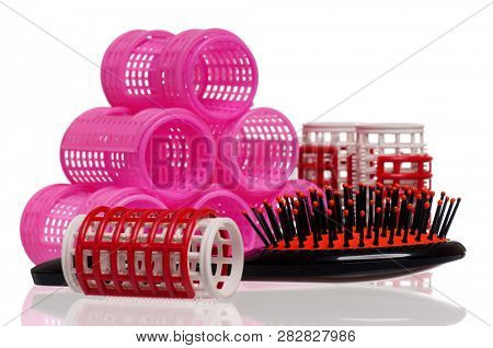 Red hair curlers and hairbrush isolated on white background poster