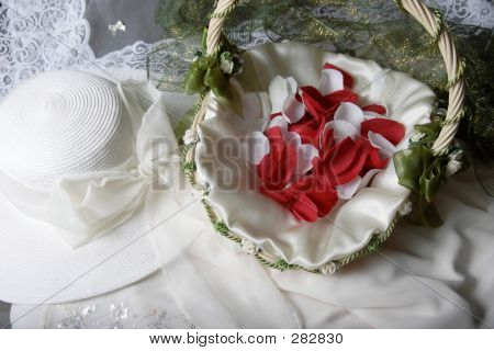 Bridal Hat Beside A Basket Of Rose Petals