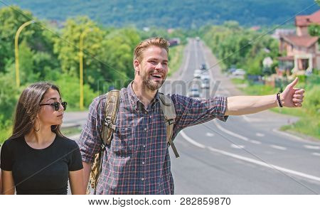 Couple Travelers Man And Girl Hitchhiking At Edge Road Nature Background. Travel By Autostop. Couple