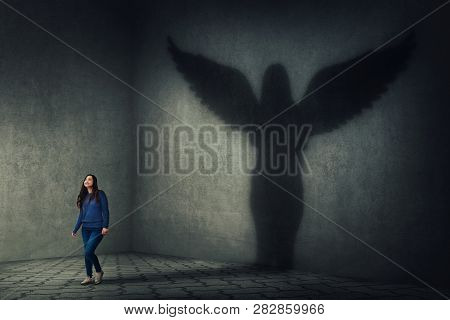 Proud And Confident Young Woman Walking And Casting A Superhero Shadow As A Guardian Angel With Wing