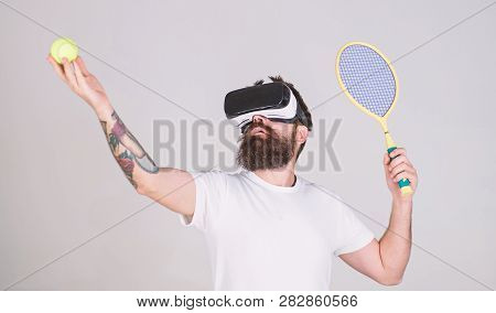 Man With Long Beard Holding Tennis Ball And Bat Isolated On Gray Background. Bearded Man In Vr Glass