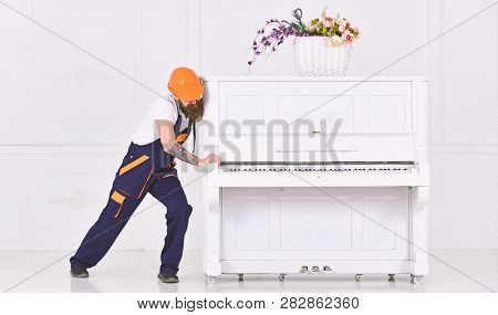 Man With Beard Worker In Helmet And Overalls Pushes, Efforts To Move Piano, White Background. Loader