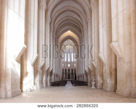 Well-lit View Of The Churchs Nave Towards The Main Chapel And Ambulatory. Alcobaca Monastery In Port