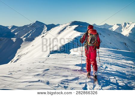 Male Ski Tourer Enjoying The View On A Summit In The Alps