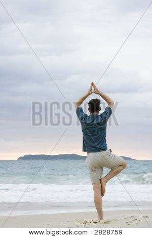 Человек делает йоги на пляже