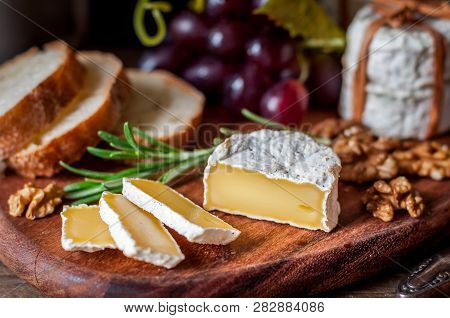 Sliced Hard French Cheese With Bread, Grapes, Herbs And Nuts