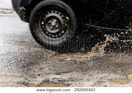 Car Driving Through A Pothole With Splashes Of Water, Montreal, Canada.