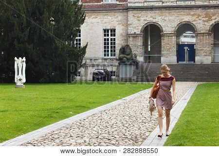 Leuven, Belgium - September 05, 2014: Unknown Young Woman On The Background Of The Pauscollege (pope