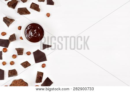 Creative Layout Made Of Chocolate Pieces , Cup With Hot Chocolate And Nuts On Wooden Background. Fla