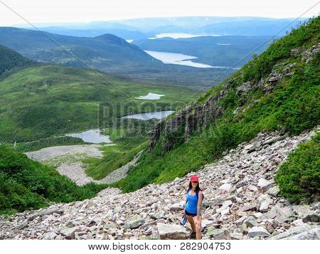 A Young Female Hiker Climbing Near The Summit Of Gros Morne Mountain, In Gros Morne National Park, N