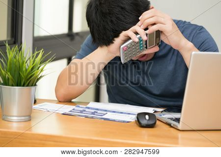 Asian Man Stressed While Calculate The Credit Card Debt With A Calculator And Working On Laptop At H