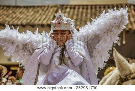 Latacunga, Ecuador - September 22, 2018 - Girl In Angel Costume Holds Her Ears Against The Loud Nois