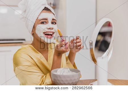 Face And Body Skin Care, Face Treatment At Home Concept. Happy Young Woman Applying A White Mask On
