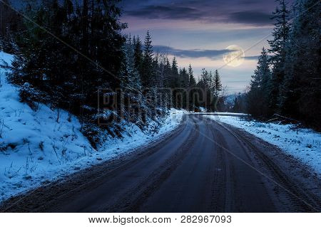 Road Through Pine Forest In Mountains At Night In Full Moon Light. Mysterious Transportation Winter