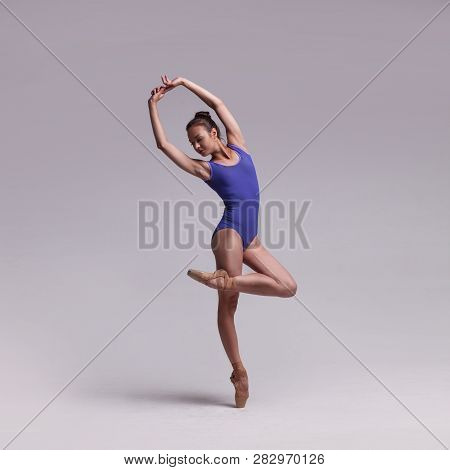 Beautiful Woman Ballet Dancer In Blue Swimsuit Posing On Isolated Light Grey Studio Background