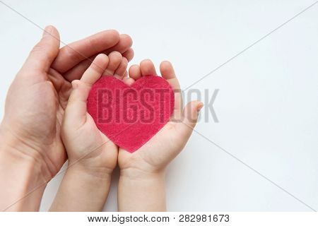 Adult And Child Hands Holding White Heart, Health Care, Donate And Family Insurance Concept, World H
