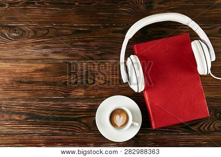 Audio Vs. Paper Book Concept. Reading Versus Listening. Books And Headphones On Table.