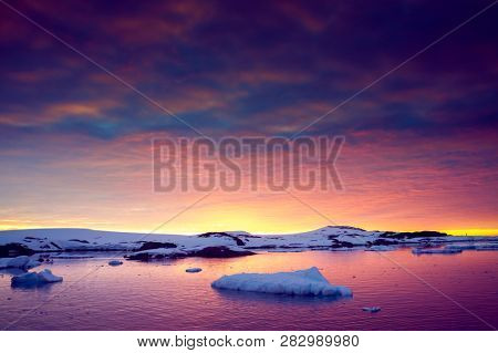 Colorful cloudy sky over the Antarctica shoreline. Overwhelming sunset view. The snow covered shore next to the frozen ocean. Ideal background for the collages in blue, purple and scarlet tints.