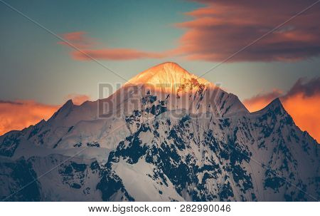 Mountain top colorful sunet, Antarctica. The sunlit snow covered range. Breathtaking polar scenery. The mighty mountain range under the bright sunset cloudy sky. Amazing South Pole landscape.