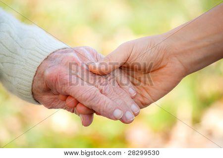 Senior und Jugendliche Hand in Hand