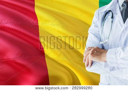 Guinean Doctor Standing With Stethoscope On Guinea Flag Background. National Healthcare System Conce