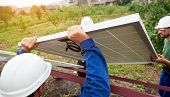 Three professional technicians connecting solar photo voltaic panel to metal platform using screwdriver on green summer background, side view. Stand-alone exterior solar panel system installation. poster