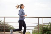 Happy jogger feeling runner high. Young woman in tights and hoody enjoying morning run. Runner high concept poster